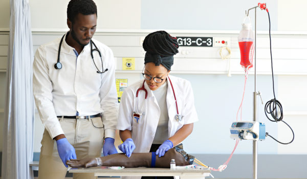 Students practising IV injection on a Phlebotomy Venipuncture Practise Arm with a medical instructor teaching the correct way in a University Hospital in Cape Town South Africa